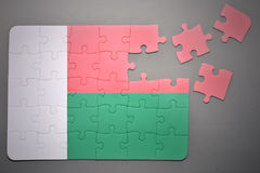 Puzzle with the national flag of madagascar. Broken puzzle with the national flag of madagascar on a gray background Stock Photos