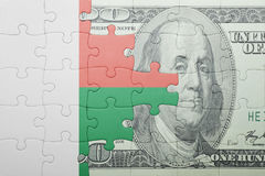 Puzzle with the national flag of madagascar and dollar banknote. Concept Stock Image