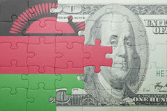 Puzzle with the national flag of malawi and dollar banknote Stock Photography