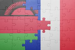 Puzzle with the national flag of malawi and france. Concept Royalty Free Stock Image