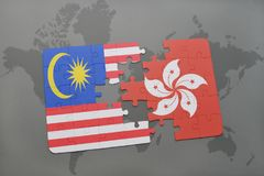 Puzzle with the national flag of malaysia and hong kong on a world map background. 3D illustration Royalty Free Stock Image