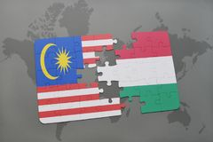 Puzzle with the national flag of malaysia and hungary on a world map background. Stock Photos