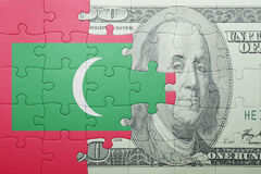 Puzzle with the national flag of maldives and dollar banknote Stock Images