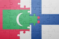 Puzzle with the national flag of maldives and finland. Concept Royalty Free Stock Photography