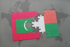 Puzzle with the national flag of maldives and madagascar on a world map. Background. 3D illustration Stock Photography