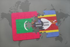 Puzzle with the national flag of maldives and swaziland on a world map Royalty Free Stock Photos