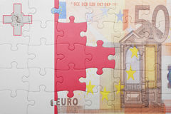 Puzzle with the national flag of malta and euro banknote. Concept Stock Image
