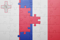 Puzzle with the national flag of malta and france. Concept Stock Image