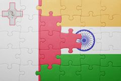 Puzzle with the national flag of malta and india. Cotncept Royalty Free Stock Photography