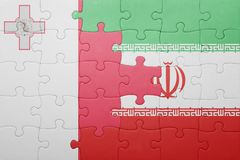 Puzzle with the national flag of malta and iran. Concept Stock Photo