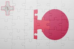 Puzzle with the national flag of malta and japan. Concept Royalty Free Stock Image