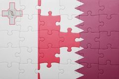 Puzzle with the national flag of malta and qatar. Concept Royalty Free Stock Photo
