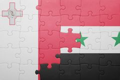 Puzzle with the national flag of malta and syria. Concept Royalty Free Stock Images