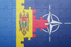 Puzzle with the national flag of moldova and nato. Concept stock photo