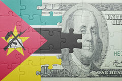 Puzzle with the national flag of mozambique and dollar banknote Stock Photo