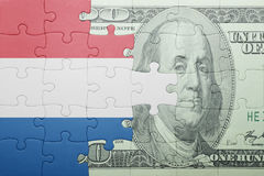 Puzzle with the national flag of netherlands and dollar banknote. Concept stock illustration