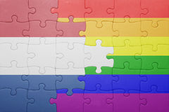 Puzzle with the national flag of netherlands and gay flag Stock Image