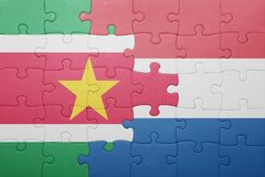 Puzzle with the national flag of netherlands and suriname. Concept Stock Photo