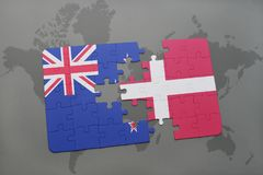 Puzzle with the national flag of new zealand and denmark on a world map background Stock Image