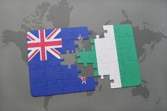 Puzzle with the national flag of new zealand and nigeria on a world map background. Royalty Free Stock Images