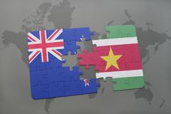 Puzzle with the national flag of new zealand and suriname on a world map background. 3D illustration Royalty Free Stock Photos