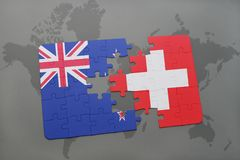 Puzzle with the national flag of new zealand and switzerland on a world map background Royalty Free Stock Photo