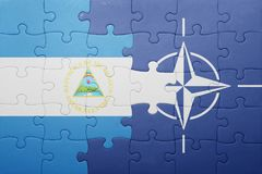 Puzzle with the national flag of nicaragua and nato. Concept stock images
