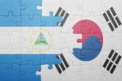 Puzzle with the national flag of nicaragua and south korea. Concept royalty free stock images
