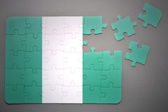 Puzzle with the national flag of nigeria. Broken puzzle with the national flag of nigeria on a gray background Royalty Free Stock Photo
