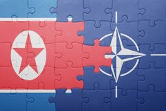 Puzzle with the national flag of north korea and nato. Concept stock photography