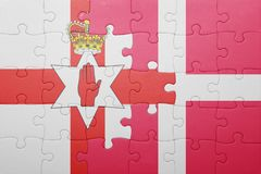 Puzzle with the national flag of northern ireland and denmark. Concept Royalty Free Stock Images
