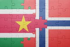 Puzzle with the national flag of norway and suriname. Concept Stock Photos