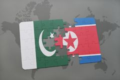 Puzzle with the national flag of pakistan and north korea on a world map background. 3D illustration stock photography