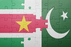 Puzzle with the national flag of pakistan and suriname. Concept Royalty Free Stock Photography