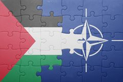 Puzzle with the national flag of palestine and nato Royalty Free Stock Image