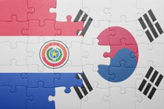 Puzzle with the national flag of paraguay and south korea. Concept stock photo
