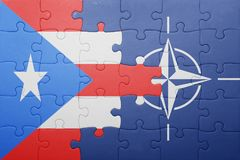 Puzzle with the national flag of puerto rico and nato Royalty Free Stock Photography