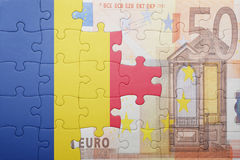 Puzzle with the national flag of romania and euro banknote Royalty Free Stock Photography