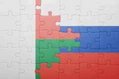 Puzzle with the national flag of russia and madagascar. Concept Stock Image