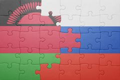 Puzzle with the national flag of russia and malawi. Concept Royalty Free Stock Photos