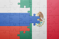 Puzzle with the national flag of russia and mexico. Concept royalty free stock photography