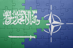 Puzzle with the national flag of saudi arabia and nato Stock Photo