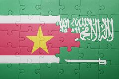 Puzzle with the national flag of saudi arabia and suriname. Concept Royalty Free Stock Photography