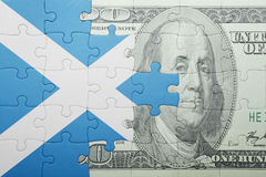 Puzzle with the national flag of scotland and dollar banknote. Concept Royalty Free Stock Image