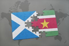 Puzzle with the national flag of scotland and suriname on a world map Stock Photography