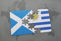Puzzle with the national flag of scotland and uruguay on a world map Stock Image