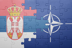 Puzzle with the national flag of serbia and nato Stock Photo