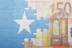 Puzzle with the national flag of somalia and euro banknote. Concept Stock Image