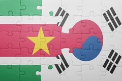Puzzle with the national flag of suriname and south korea. Puzzle with the national flag of and south korea . concept royalty free stock photography