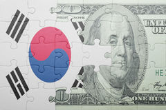 Puzzle with the national flag of south korea and dollar banknote. Concept stock photography